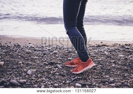 Legs And Sneakers On The Sea Beach.