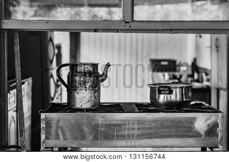Old Kitchen with a kettle and a cooking pot on a stove viewed through a window