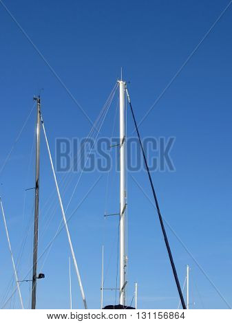 Sailboat masts in the marina against a blue summer sky