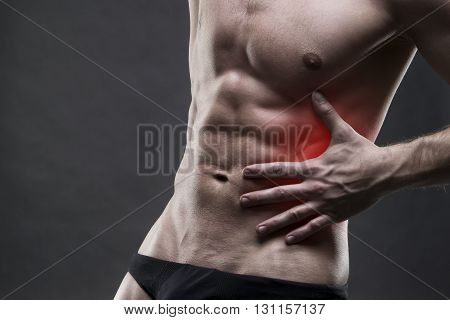 Pain in the left side. Muscular male body. Handsome bodybuilder posing on gray background with red dot