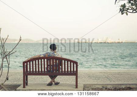 asian man sitting wood chair side sea old film tone stlye