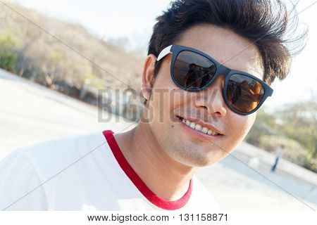 young asian handsome man standing and smile on side sea background Thailand