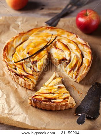 Apple tart with vanilla pod on a white plate Traditional holiday dessert Wooden rustic background