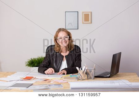 Cheerful middle-aged designer behind a desk filled with documents and plans in a home office