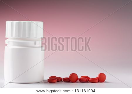 White plastic pill bottle and heap of round red pills