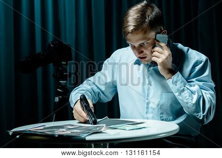 Angry man holding gun talking on cellphone pictures lying on a table