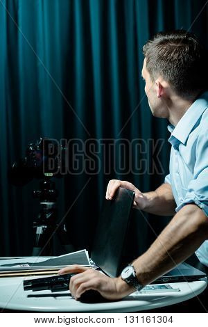 Man standing beside table holding gun and laptop pictures lying on a table
