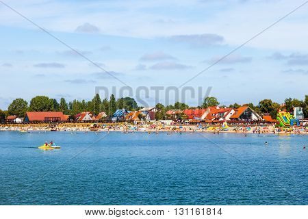 HEL, POLAND - AUGUST 10, 2015: Sandy beach scene of many people suntanning, relaxing and enjoying the shore in summer day. Hel is one of most famous cruise travel destinations in Poland.