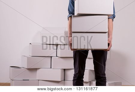 Cropped picture of a man holding three white boxes