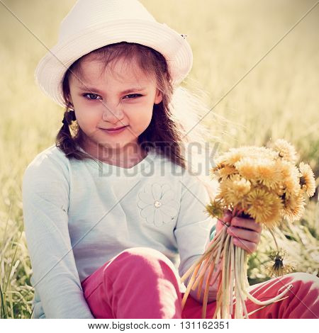 Funny Grimacing Kid Girl In Fashion Hat Siiting On The Grass And Holding Yellow Flowers. Toned Close