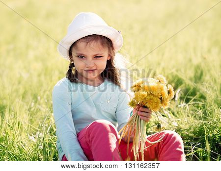 Funny Grimacing Kid Girl In Fashion Hat Siiting On The Grass And Holding Yellow Flowers