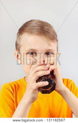 Little funny blonde boy drinking a fresh cola