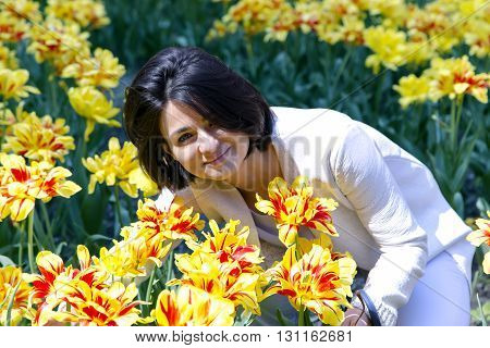 Pretty smiling brunette in a white suit among yellow spring tulips