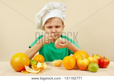 Little funny boy eat acidic orange at the table with fruits