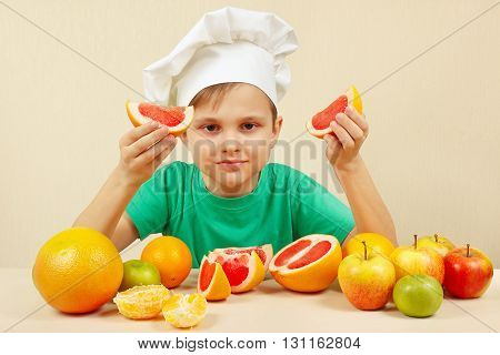 Little boy in chefs hat with two slices of grapefruit at the table with fruits