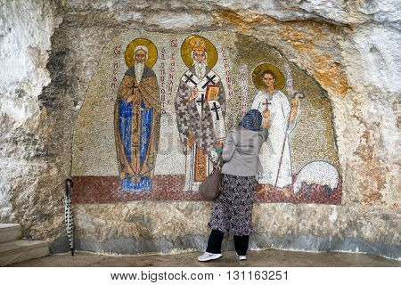 OSTROG MONTENEGRO - May 15 2016: unidentified woman prays at the Mosaics Wall paintings in Serbian Orthodox Ostrog monastery Montenegro. Ostrog is the most popular pilgrimage place in Montenegro.