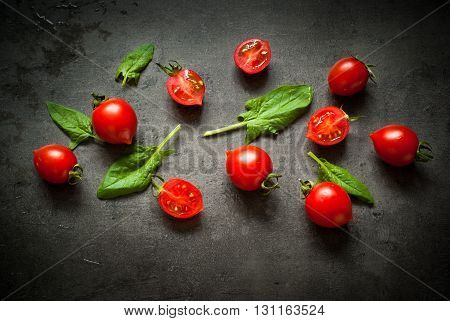 Tomatoes and spinash at slate background. Healthy eating and Diet concept. Vegan food background.