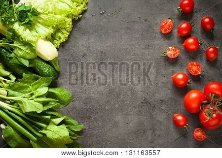 Green and red vegetables at slate background with space for text. Healthy eating and Diet concept. Vegan food background.