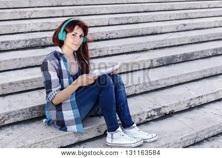 Girl reads clipboard sitting on school steps listen to music on headphones.