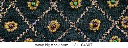 Close up detail of vintage sari fabric with embellishments.Diamond and flower design.