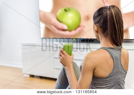 Healthy eating woman drinking green smoothie watching television online education tv show about nutrition and weight loss. Girl sitting at home learning about losing weight with vegetables and fruits.