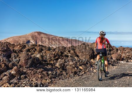 Mountain biking woman MTB cyclist cycling on nature volcano volcanic trail on vacation travel against mountains. Tourist doing sports activity during summer holidays. Leisure tourism, ecotourism.