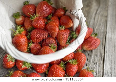 Strawberry falling from a basket on a wooden table. Close-up.