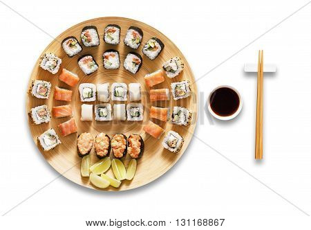 Japanese food restaurant, sushi maki gunkan roll plate or platter set. Chopsticks, ginger, wasabi and soy sauce. Sushi at bamboo round plate isolated at white background.