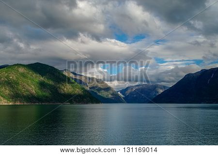 Cloudy Sky Over Banks Of Fjord. Mountains With Green Forest, Eidfjord, Norway