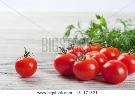 Cherry tomatoes and green dill on a wooden table