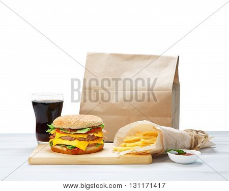 Fast food. Brown wrapping paper package with copyspace. Hamburger, potato fries, cola drink. Takeaway food. Wrapped French fries, packaging, Cola glass, double cheese hamburger at wood isolated