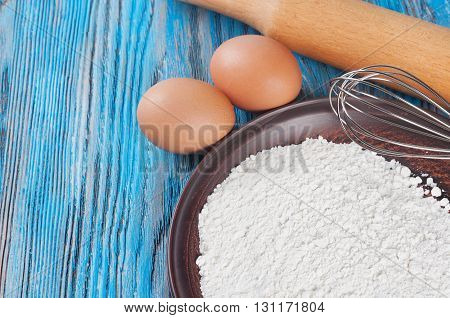 Eggs and flour on a blue wooden background