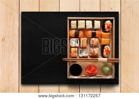 Japanese food restaurant, sushi maki gunkan roll plate or platter set. Chopsticks, ginger, soy sauce, wasabi. Sushi on wooden table background and black mat, take away, delivery box. Top view.