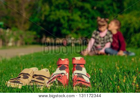 sandals on a green grass on a background the boy with the girl
