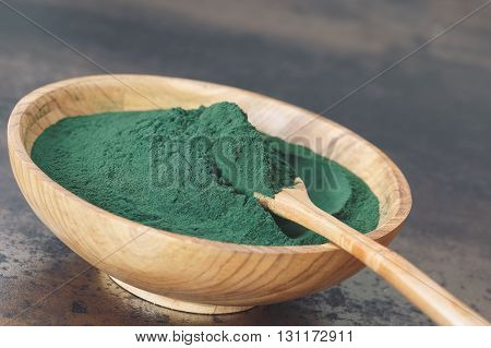 Spirulina Algae Powder, close up. Spirulina powder in wooden bowl with spoon. Macro, selective focus, blank space