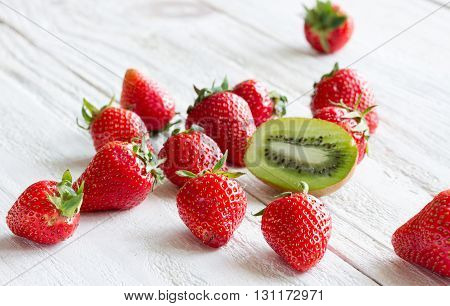 fresh sweet strawberry with kiwi on light wooden background