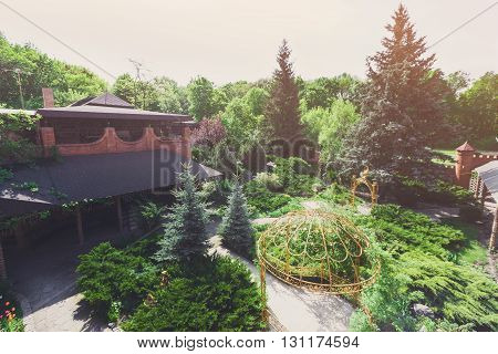 Beautiful landscape design, garden path with stone tiles, evergreen bushes, fir trees, blue spruces and shrubs in sunlight. Modern landscaping near castle. Summer garden or park design.