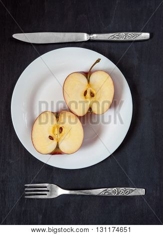 Apple on a white plate with knife and fork on a dark background. Two halves of an apple on a white plate with knife and fork on a dark background. healthy Eating