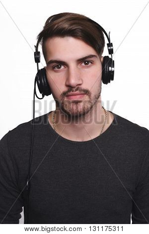 Portrait of young handsome man listening to music. Isolated white background.
