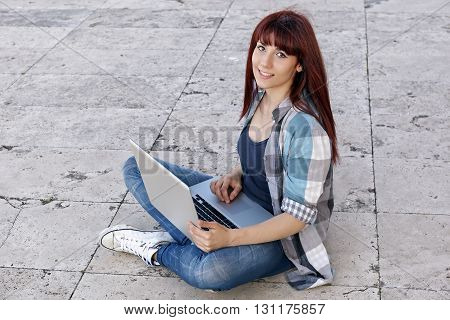 Girl sitting on the floor working on laptop.