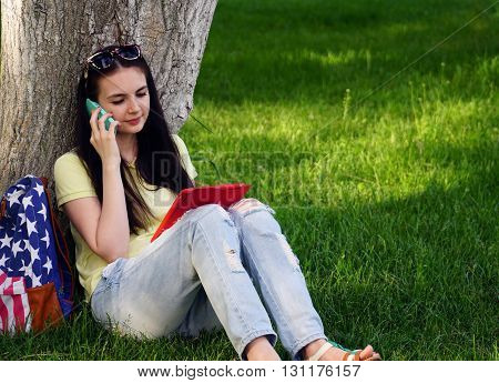 young beautiful woman sitting near a tree on the grass in the park and use the app in your comuter tablet