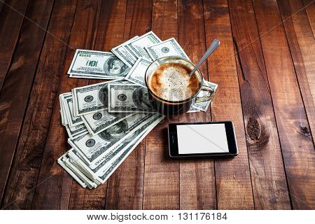 Coffee cup money dollars and phone on vintage wooden table background. Business concept.