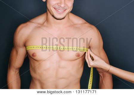 Woman measuring man's chest with a yellow centimeter. Man is smiling.