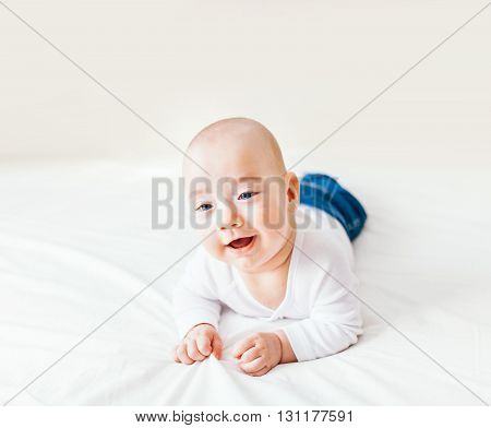 Happy baby boy giggling and lying in bed