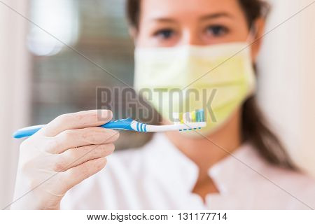 Blurry pose of a young dentist holding a blue toothbrush in hand . Focus on the toothbrush