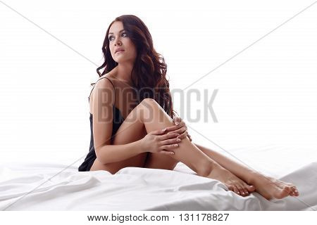 Photo of attractive young brunette sitting in bed. Isolated on white