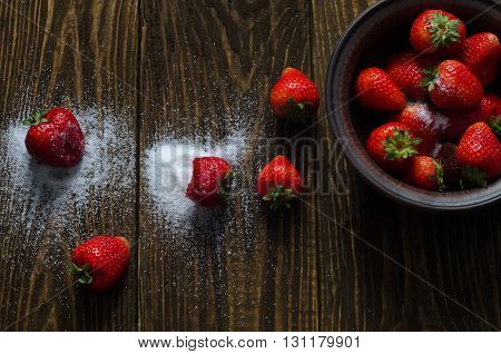 Juicy strawberries in sugar lies on a black background.