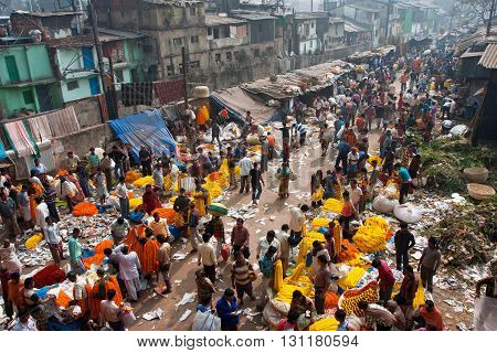 KOLKATA, INDIA - JAN 11, 2013: People move through giant Mullik Ghat Flower Market on January 11, 2013. The market is more than 125 years old. More than 2000 sellers work in the market every day