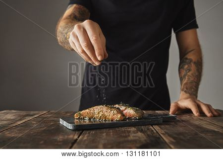 Man Cooks Healthy Meal On Rustic Wooden Table, Salts Two Raw Pieces Of Salmon In White Wine Sause Wi