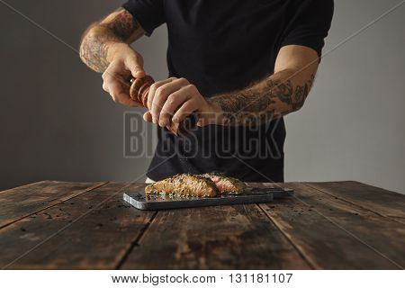 Man Cooks Healthy Meal On Rustic Wooden Table, Peppers Two Raw Pieces Of Salmon In White Wine Sause